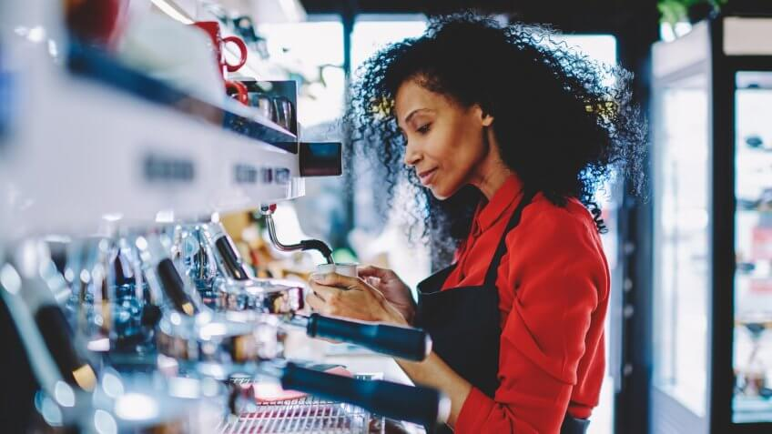 Professional female barista with dark skin standing at bar on working place and preparing tasty beverage on order.