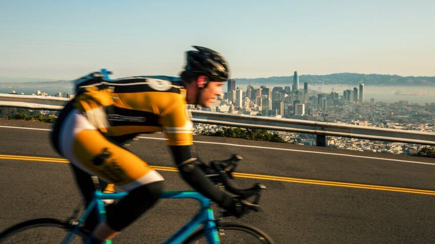 Man bicycling on Twin Peaks in San Francisco with downtown in background.