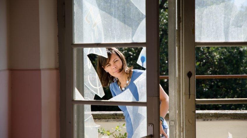 Woman watching inside through a broken window.