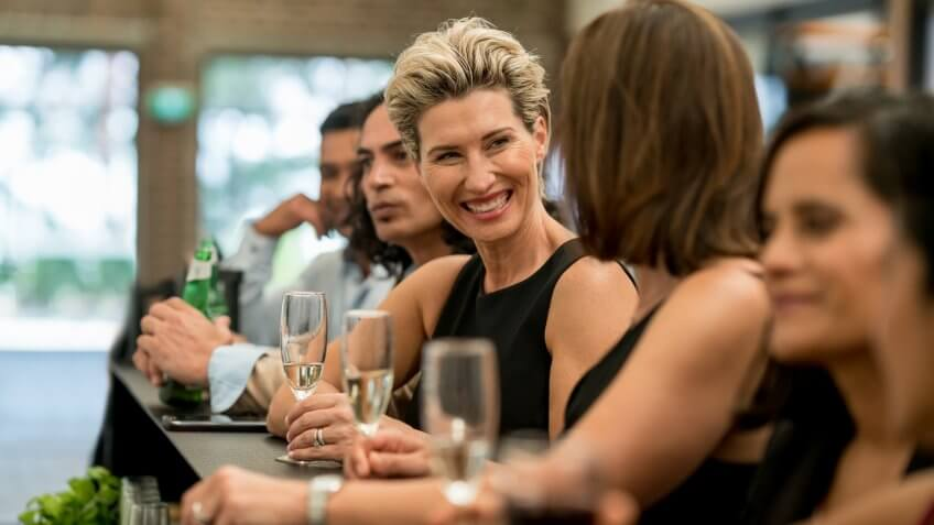 Happy group of business people having drinks at a bar and laughing – lifestyle concepts.