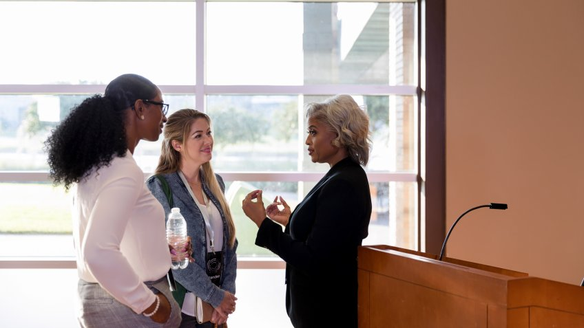 Mature female business conference keynote speaker talks with interested businesswomen after conference.