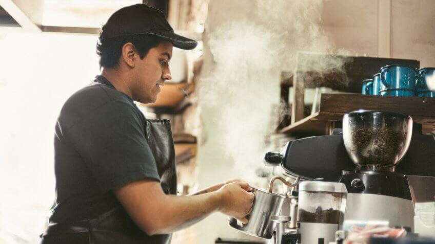Mexican Barista warming milk with a Coffee Seamer in Coffeeshop.