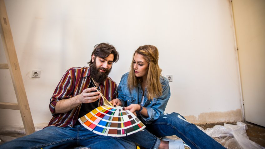 Hipster couple painting a house, sitting on the floor and choosing colors from a color swatch.