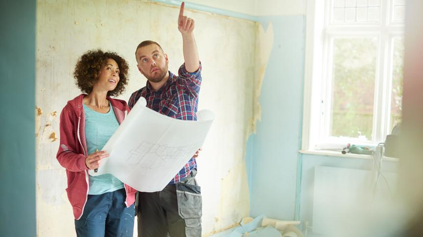 a young couple take time out from scraping walls in her new house to check against their architect plans.