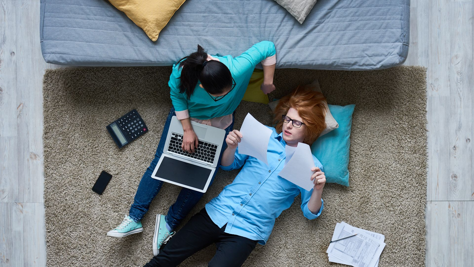 Tired redhead guy lying on carpet and reading tax documents while his girlfriend listening to him and using laptop.
