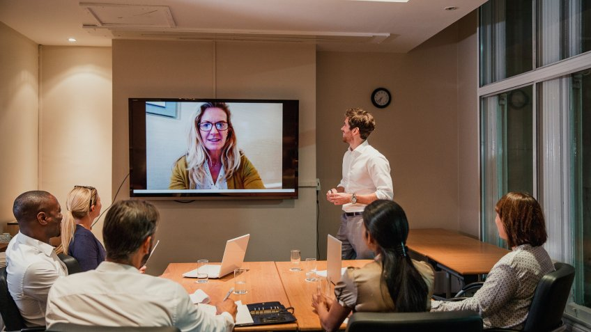coworkers having video meeting with remote employee
