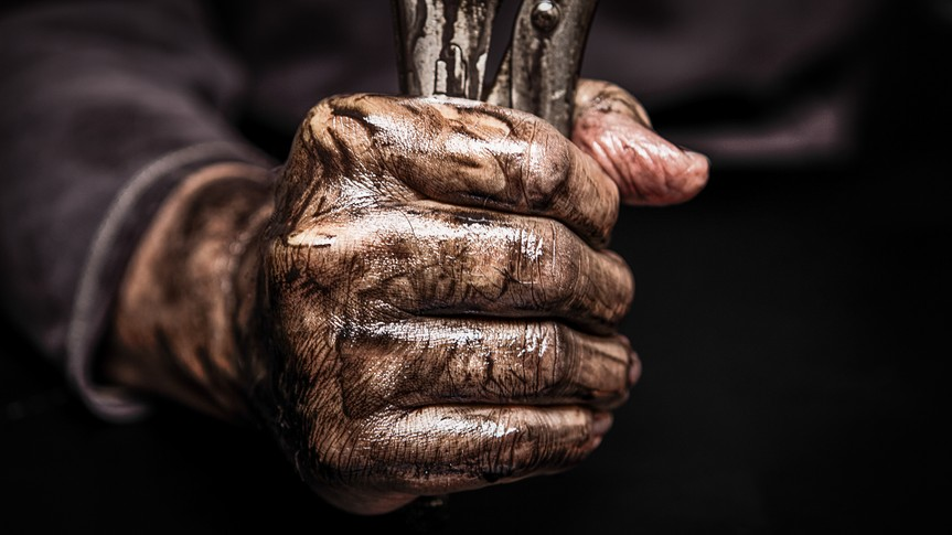 Mechanic holding a wrench in his dirty hands.