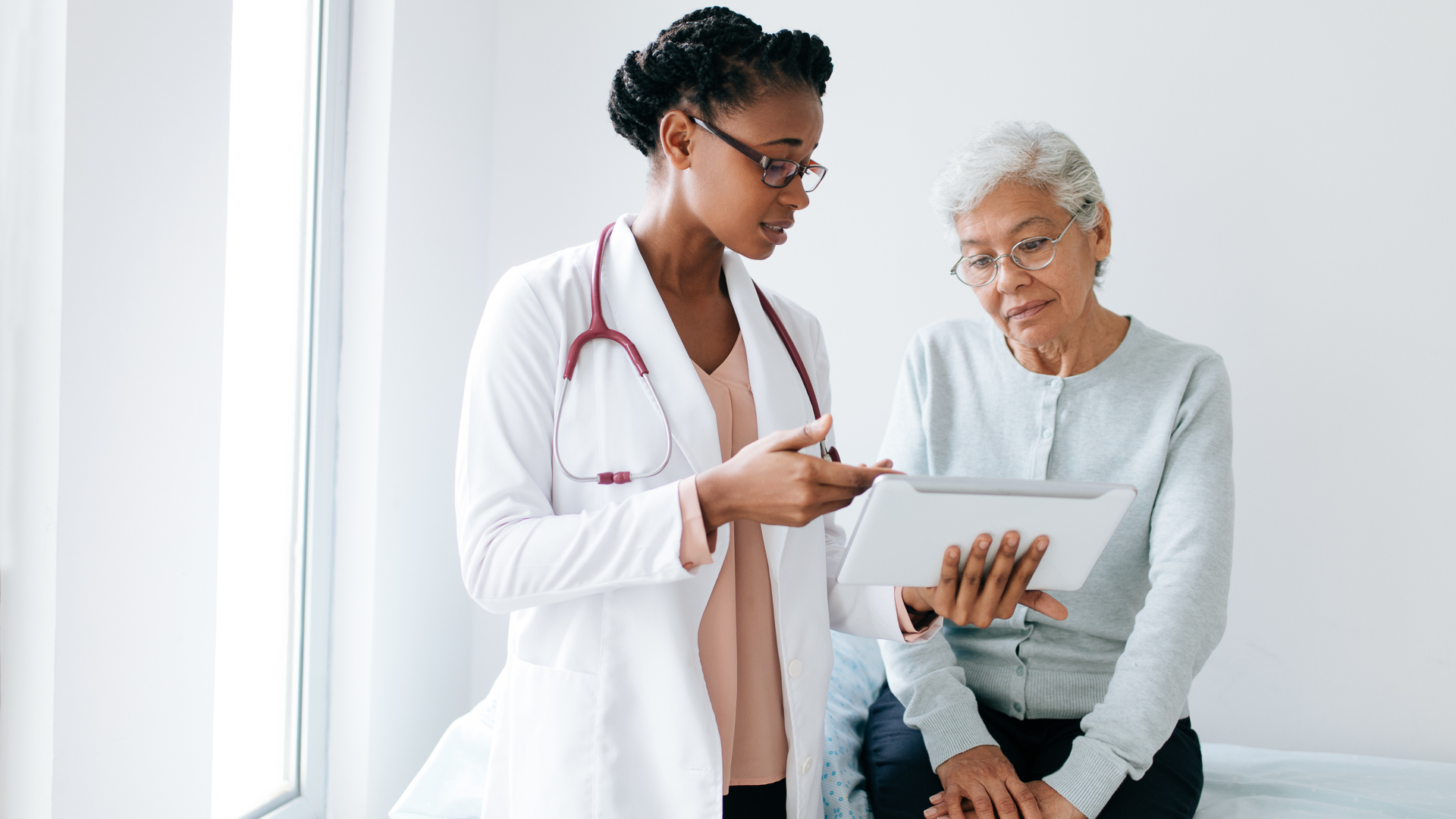 A black female doctor standing next to female patient and showing her something on digital tablet.