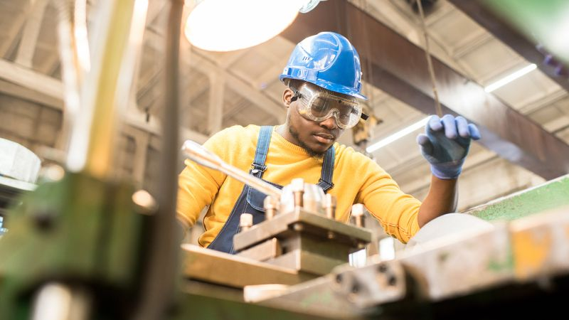 Serious busy young black factory engineer in hardhat and safety goggles examining milling lathe and repairing it while working at production plant.