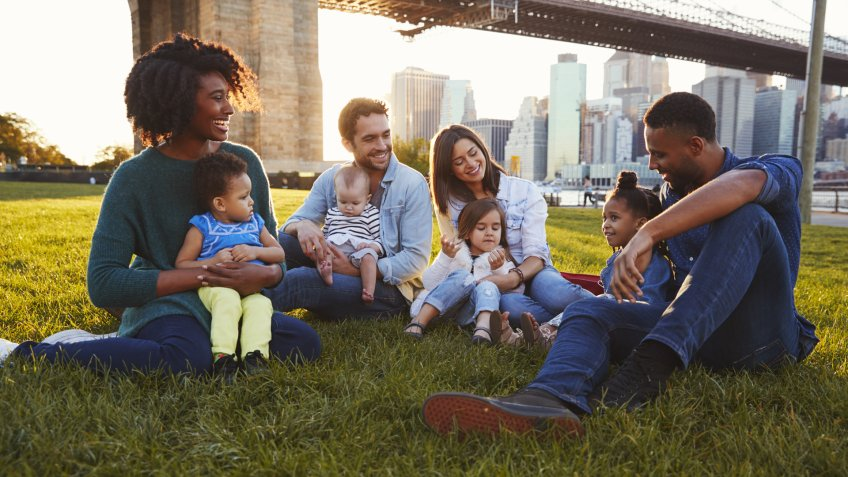Two families with daughters sitting on lawn.