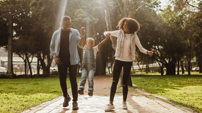 Happy beautiful family of three walking in park.
