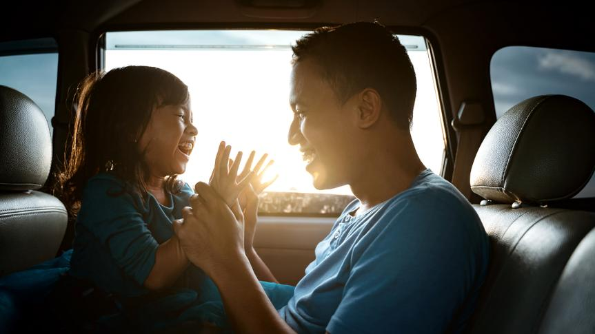 lovely asian daughter with father in the car playing together laughing.