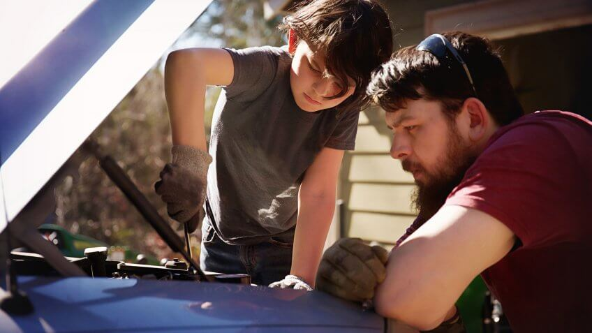 Father teaching son to work on a truck.