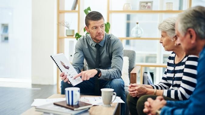 Shot of senior couple having a consultation with a financial advisor at home.