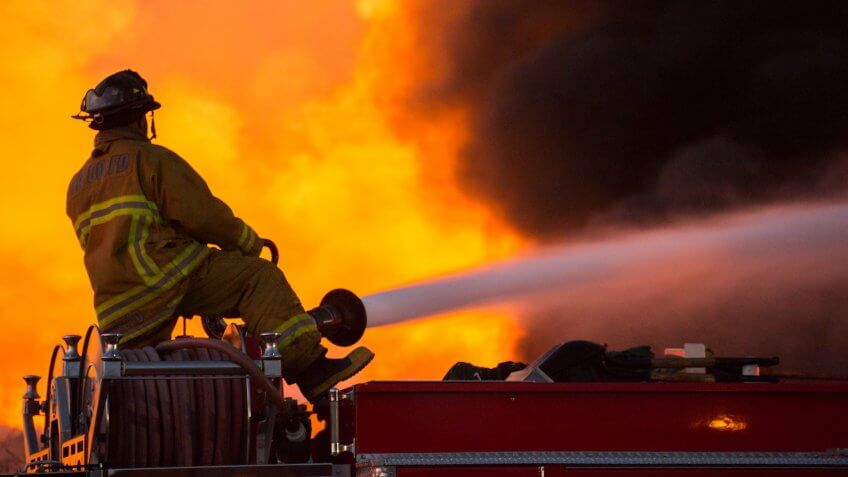 Santa Fe Springs, California - May 29, 2014: Firefighters try to douse the flames of a recycling sorting facility on fire.