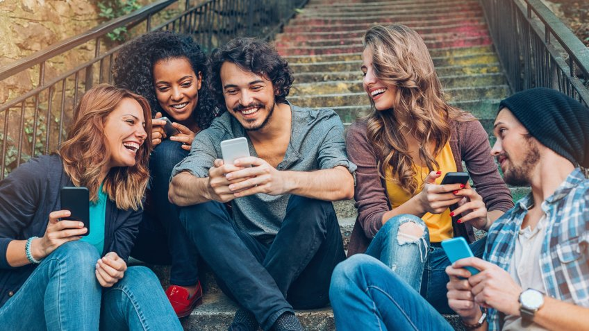 Multi-ethnic group of friends with smart phones sitting on a staircase.