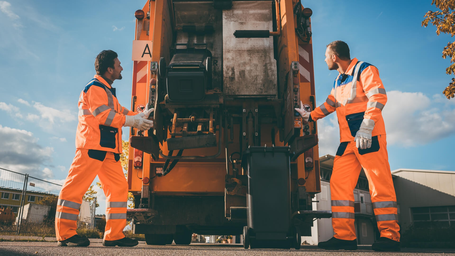 Two refuse collection workers loading garbage into waste truck emptying containers.