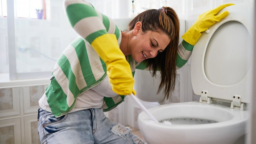 young woman cleaning a bathroom toilet.