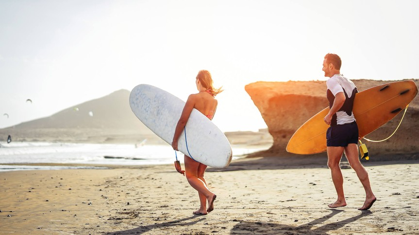 Surfers couple running together with surfboards on the beach at sunset - Sporty friends having fun going to surf - Travel, vacation, sport lifestyle concept.