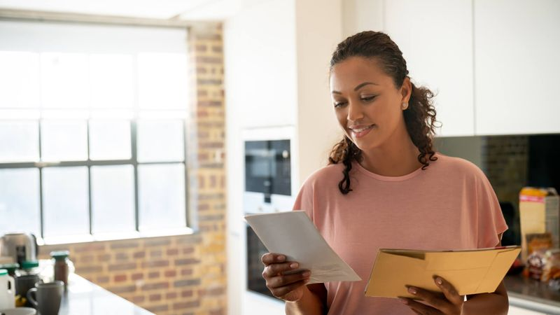 Portrait of a happy woman reading her mail at home and smiling – lifestyle concepts.