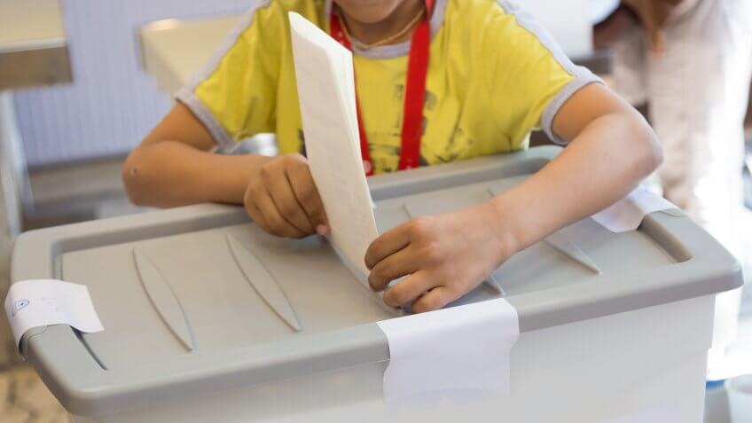 kid putting ballot in fake ballot box