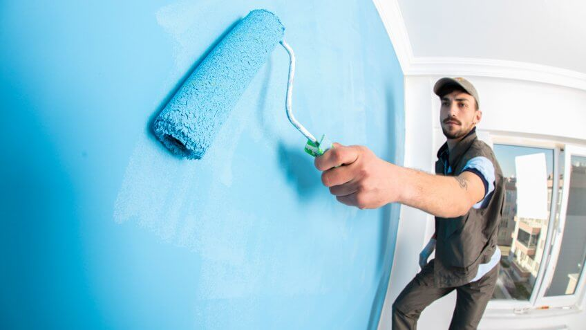 Young man painting a wall blue with a roller.