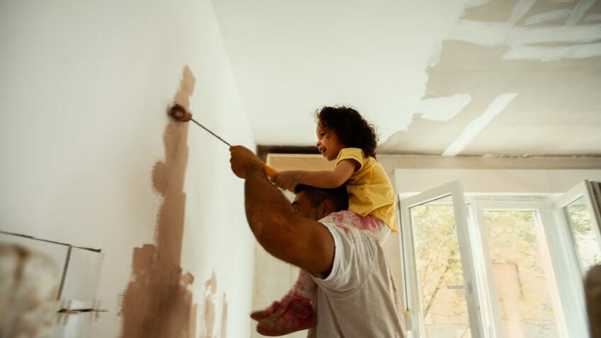 Young family renovating their home, painting wall.