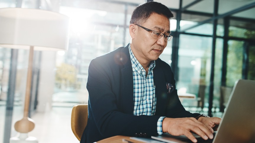 Shot of a mature businessman working on a laptop in an office.