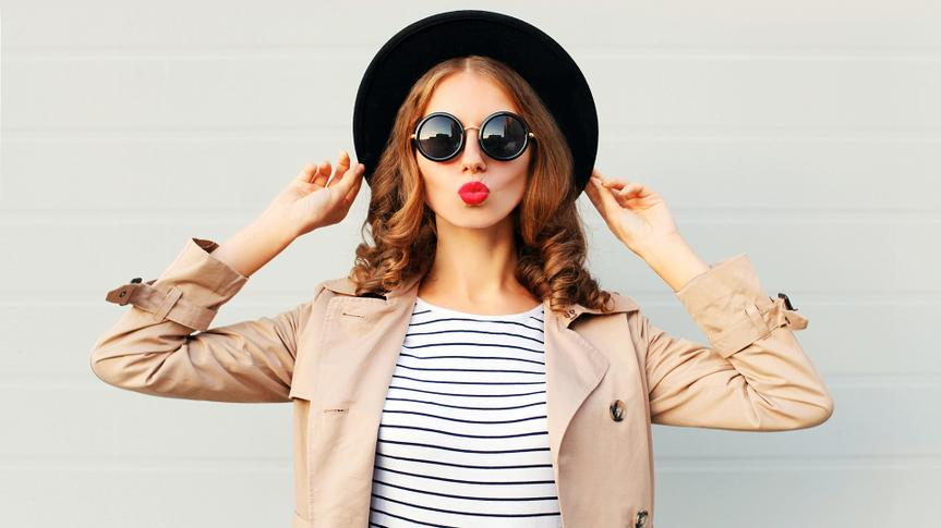 Fashion portrait pretty sweet young woman blowing red lips wearing a black hat sunglasses coat over grey background.