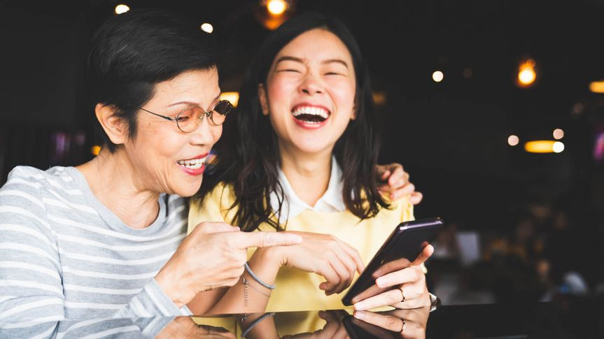 Asian mother and daughter laughing and smiling on a selfie or photo album, using smartphone together at restaurant or cafe, with copy space.