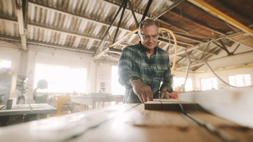 older man in wood shop creating furniture hobby