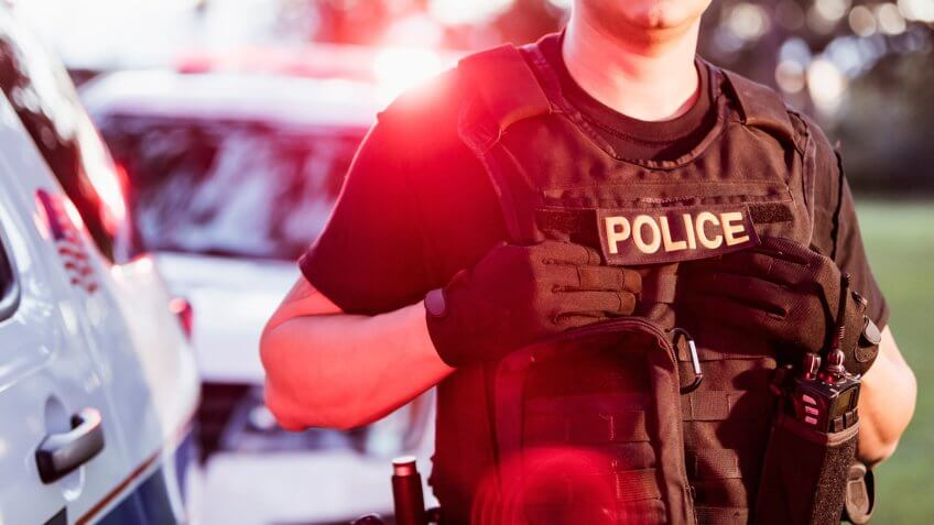 Cropped view of an Hispanic police officer wearing a bulletproof vest, standing beside two police cars.