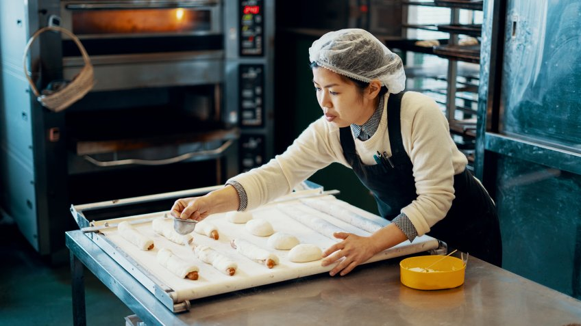Mid adult woman baking bread in an industrial kitchen in Japan.