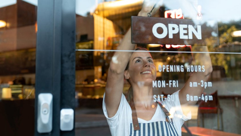 Portrait of a happy business owner hanging an open sign on the door at a cafe and smiling - food and drinks concepts.