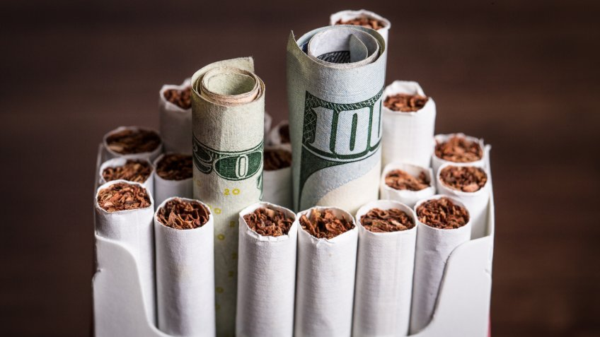 Cigarette concept with money cash replacing cigars.