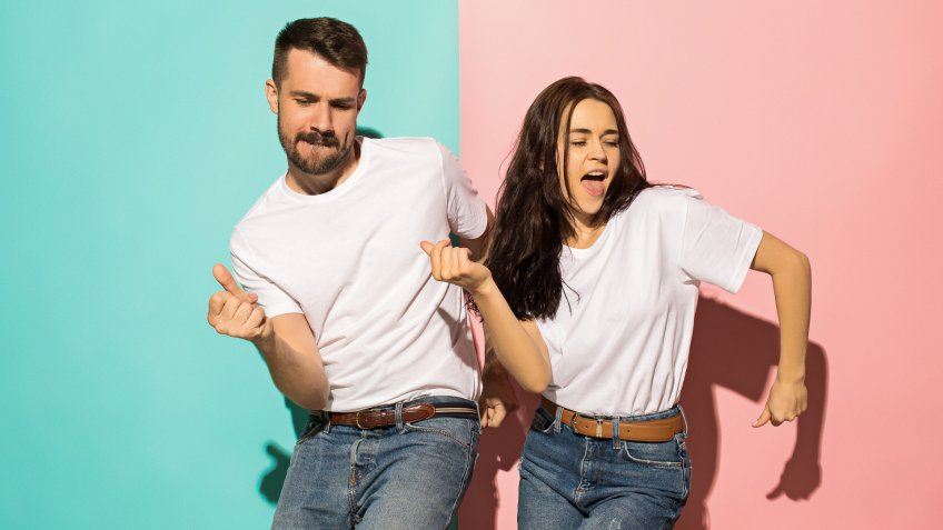A couple of young funny and happy man and woman dancing hip-hop at studio on blue and pink trendy color background.