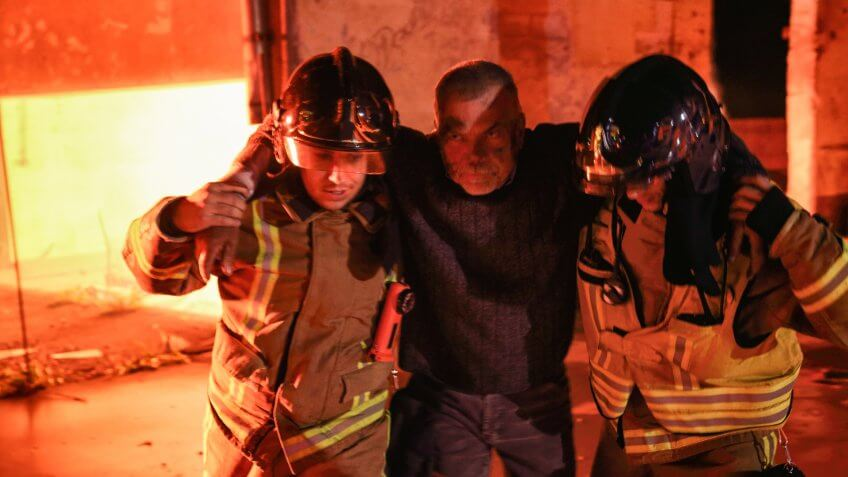 Two firefighters rescuing a victim of a fire with arms around them and helping him to walk away from the fire.
