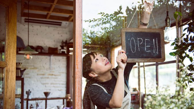Woman hanging an open sign.