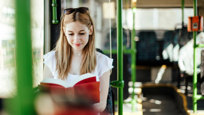 Blonde student girl is reading a book while commuting.