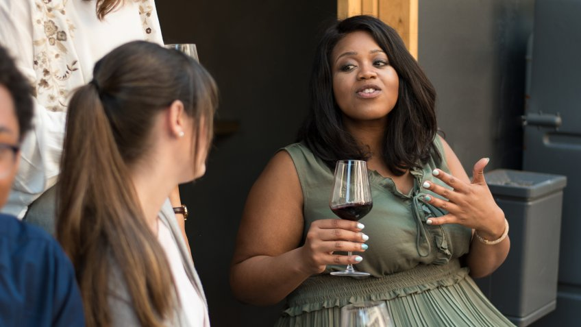 A candid shot of a young African American woman with wine talking with a group of international friends.