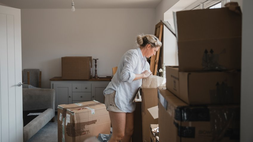 Mature woman is unpacking boxes in her new home.