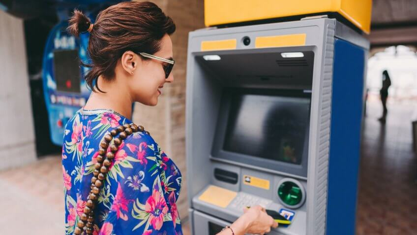 Tourist on vacation withdrawing money on ATM with smartphone.
