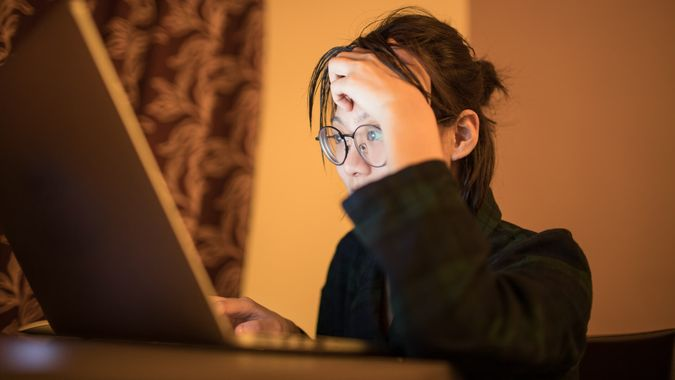 female college students using laptop late at night in search for information online.