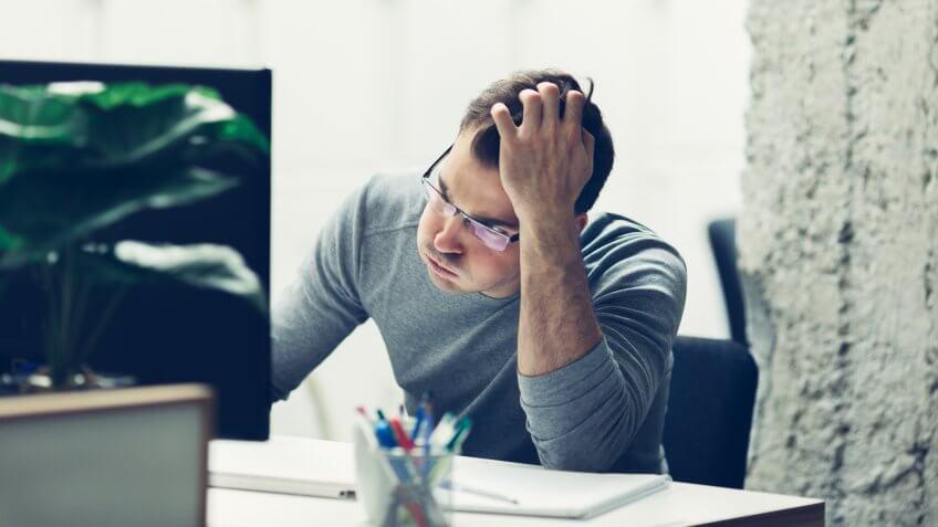 Worried businessman working in office.