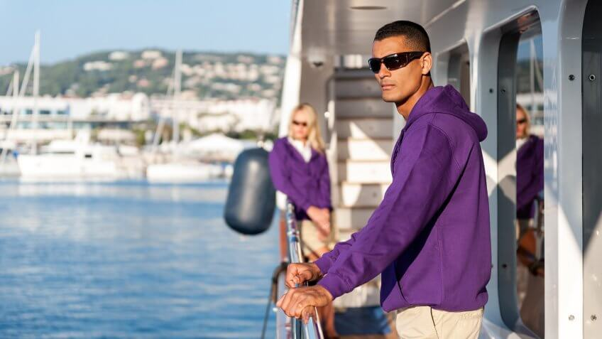 Horizontal color image of crew members standing on luxury yacht boat at harbor during sunny day.