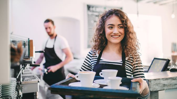 Young beautiful girl carrying cups of coffee on a tray and her colleague operating espresso machine in a coffee shop.