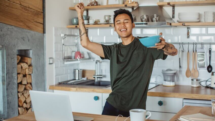 Young student prepare breakfast and dancing around table, he prepare for exams, classes are hard, he need to study more.