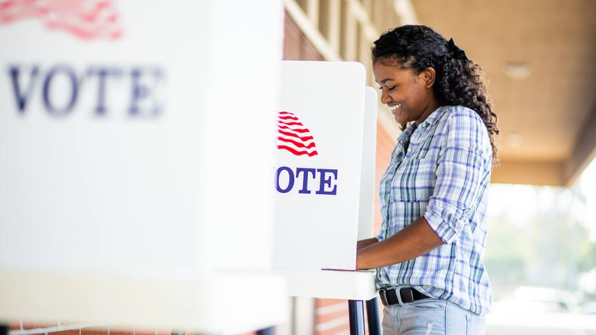 A young black girl voting on election day.