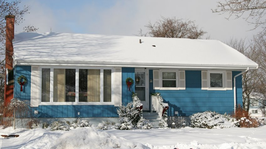 A small 1970's or late 60's bungalow decorated for Christmas and covered in snow.