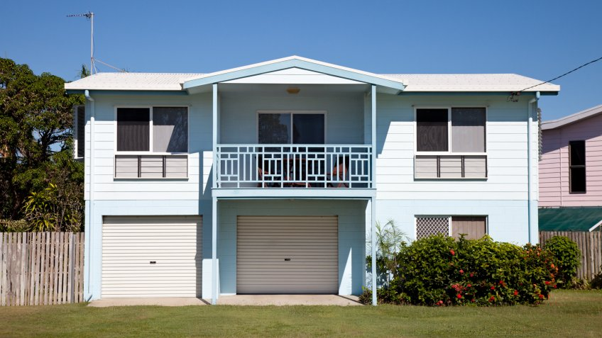 """""""Tidy two story basic Australian home built around the 1980aas, with blue sky and green grass."""